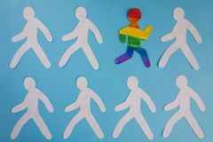 The paper man painted in the colors of the LGBT flag runs out of the gray mass stock illustration