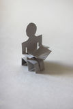 Paper man reading book on light background Royalty Free Stock Images