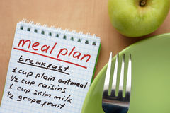 Paper with meal plan and apple. Stock Photos