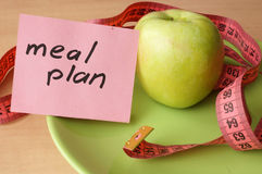 Paper with meal plan, apple and measuring tape. Royalty Free Stock Photos