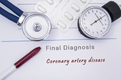 Paper medical form with a text diagnosis of Coronary artery disease on which lie the stethoscope, blood pressure monitor, white ta. Blets or pills in a blister royalty free stock photography