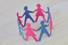 Paper men and women cut-out in a circle holding hands - Gender relationship concept. Paper men and women cut-out in a circle holding hands. Gender relationship royalty free stock image