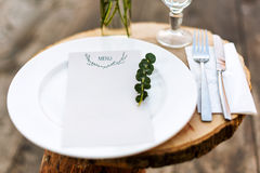Paper menu on decorated table ready for dinner. Beautifully decorated table set with flowers, plates and serviettes for outdoor we Royalty Free Stock Images