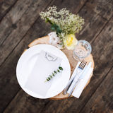 Paper menu on decorated table ready for dinner. Beautifully decorated table set with flowers, plates and serviettes for outdoor we Royalty Free Stock Photos