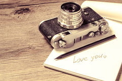Paper with message I love you and retro camera Royalty Free Stock Photo