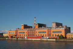 Paper mill building on the river bank. Against blue sky Royalty Free Stock Photography