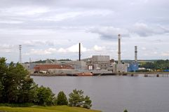 Paper mill on river. A view across the Penobscot River to a large paper manufacturing mill in Bucksport, Maine on a cloudy day stock images