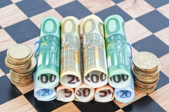 Paper money and coins as the euro on the chessboard. Royalty Free Stock Photography