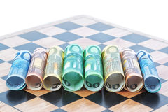 Paper money in the form of the euro on the chessboard. Stock Photos