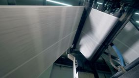 Printed newspaper moving on a rolling conveyor, bottom view. Paper moving on a rolling conveyor