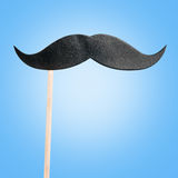 Paper mustache on a stick. On a blue background Stock Photos