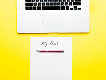 Paper My Book, pen and laptop. Photo of sheet of paper My Book, cool laptop and metallic pen on the wonderful yellow studio background stock photography