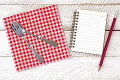 Paper napkin with cute fork, spoon on it next to a blank white notebook. Top view of red gingham paper napkin with cute fork, spoon on it next to a blank white Stock Photos