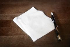 Paper napkin and pen on table stock photos