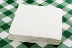 Paper napkins. Closeup of a stack of paper napkins on top of a tablecloth stock images
