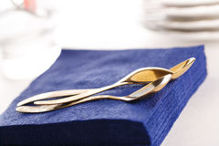 Paper napkins with spoons, plates and glasses Royalty Free Stock Photo