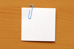Paper note. With a blue clip over the wooden table Royalty Free Stock Photo