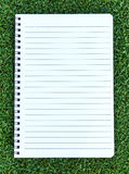 Paper note book  put on Grass. Background Royalty Free Stock Photos