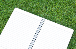 Paper note book  put on Grass. Background Stock Photo
