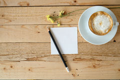 Paper note and cup of cappuccino coffee. White empty paper note and pencil and yellow flowers with the cup of cappuccino coffee. There are on wooden table Royalty Free Stock Images