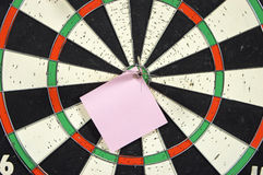 Paper note on dart board. Dart board with pinned paper note Stock Photo