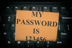 Paper note with easy password on black computer keyboard. Internet security concept. Close up royalty free stock photography