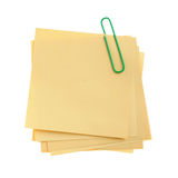 Paper note with green clinch. It is attached red pin on a white background Stock Images
