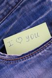 Paper note with the inscription I love you, with love peeps out of the pocket of jeans trousers. The concept of the day of lovers. Stock Photography