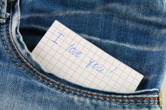 Paper note with the inscription I love you, with love peeps out of the pocket of jeans trousers. The concept of the day of lovers. Royalty Free Stock Images