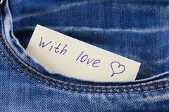 Paper note with the inscription I love you, with love peeps out of the pocket of jeans trousers. The concept of the day of lovers. Royalty Free Stock Photography