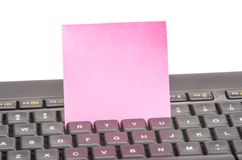 Paper note on keyboard. Blank paper note on a black keyboard stock photography