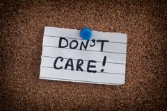 Paper note with the phrase Don`t Care on bulletin board Stock Photography