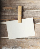 Paper note with a pinch. On wooden background Royalty Free Stock Photo