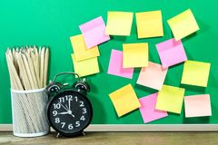 Paper note or post it on chalk board with metal cup of pencils a. Nd alarm clock.  Business table concept Stock Image