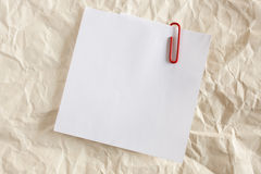Paper note with red clip. On Old Crumpled Paper Royalty Free Stock Photo