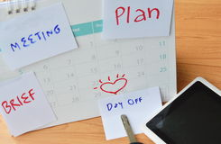 Paper note for remind stick on calendar and tablet computer with car key Stock Photo