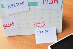 Paper note for remind stick on calendar and tablet computer Stock Photography