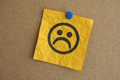 Paper note with sad face. Closeup royalty free stock photography