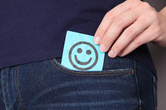 Paper note with smiling face in pocket of jeans Stock Photos