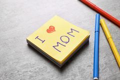 Paper note with text I LOVE MOM and felt-tip pens on table. Mother's Day celebration stock image