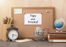 Paper note with tips and tricks word on cork board with alarm. Clock, book, money on wooden desk royalty free stock photo