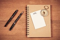 Paper note with vintage compass and dairy. Book on table royalty free stock image