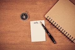 Paper note with vintage compass and dairy book. On table stock photography