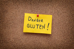 Paper note with the words Danger Gluten on cork board Royalty Free Stock Photos