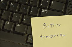 Paper note write better tomorrow stick on computer notebook for cheer up. Paper note write better tomorrow stick on the computer notebook for cheer up Stock Images