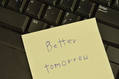 Paper note write better tomorrow stick on computer notebook for cheer up. Paper note write better tomorrow stick on thr computer notebook for cheer up Stock Image