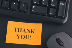 Paper note with writing Thank You! on a desk with black keyboard. Thank You!. Paper note with writing Thank You! on a desk with black keyboard and grey wireless Stock Photos