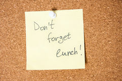 Paper note written with Don`t Forget Lunch inscription on cork board. Royalty Free Stock Photography