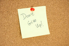 Paper note written with DON`T GIVE UP inscription on cork board Stock Images