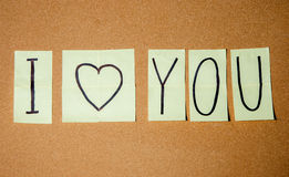 Paper note written with I LOVE YOU inscription on cork board. Stock Photography
